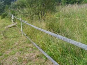 забор с закрепленными жердями